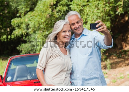 Cheerful mature couple taking pictures of themselves leaning against their cabriolet - stock photo