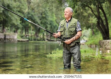 Cheerful mature fisherman fishing in a river outdoors - stock photo