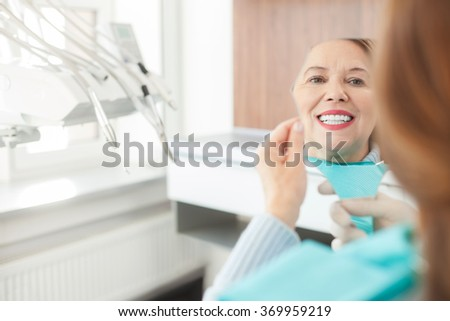 Cheerful mature lady is checking work of orthodontist - stock photo