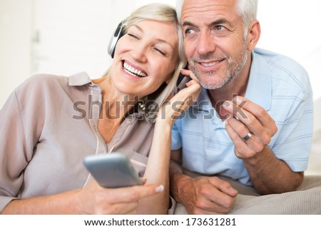 Cheerful mature man and woman with headphones and cellphone sitting on sofa at home - stock photo