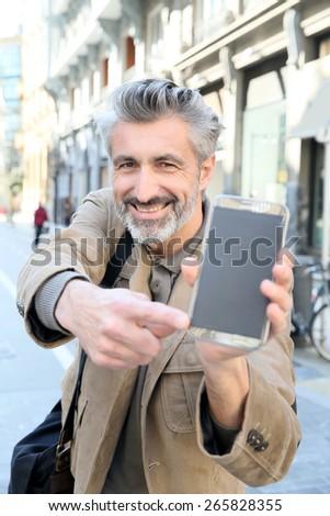 Cheerful mature man showing smartphone to camera - stock photo