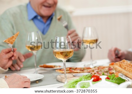 Cheerful mature parents are dining with son