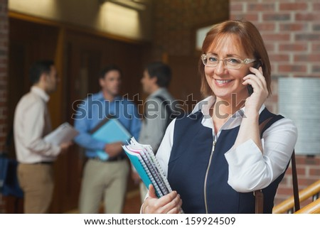 Cheerful mature student phoning with her smartphone in the corridor