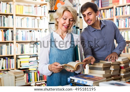 cheerful mature woman and young man having books in hands in book shop