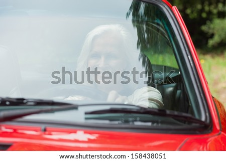 Cheerful mature woman driving red cabriolet on sunny day
