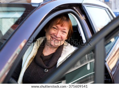 Cheerful mature woman sitting in new car at driver seat - stock photo