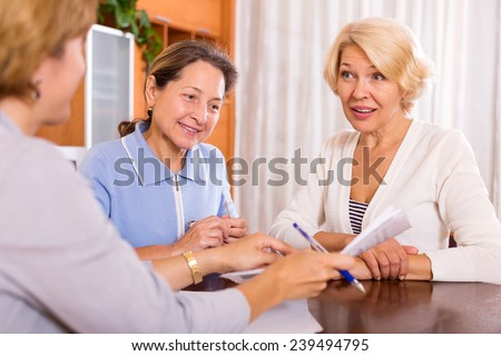 cheerful mature women consulting at insurance agent office - stock photo