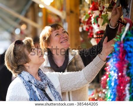 Cheerful mature women walking on the Christmas market and choosing jewelry - stock photo