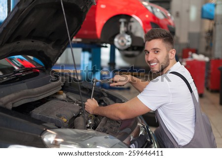 Cheerful mechanic using a ratchet wrench - stock photo