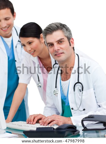 Cheerful medical team working at a computer against a white background