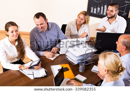 Cheerful meeting in modern office during conference call - stock photo