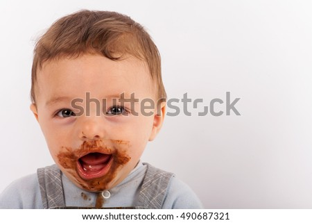 Cheerful messy baby boy with face covered in chocolate