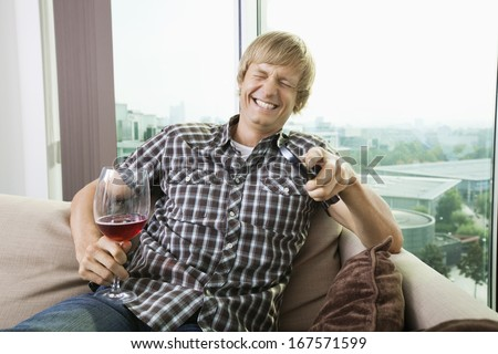 Cheerful mid-adult man with wine glass watching television on sofa at home - stock photo