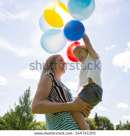 Cheerful mid adult mother and daughter playing with colorful balloons against cloudy sky - stock photo