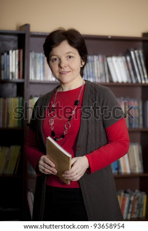 Cheerful mid-adult woman in the library. Professor, mature student, or librarian - stock photo