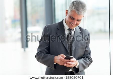 cheerful mid age businessman using smart phone  - stock photo