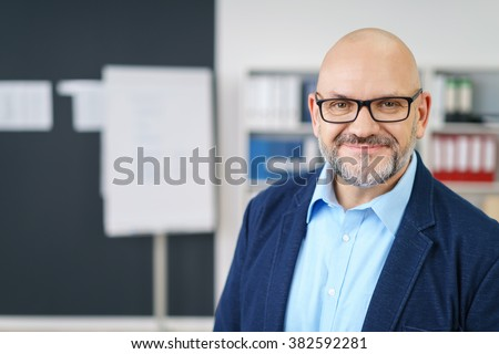 Cheerful middle aged handsome businessman with beard and bald head in business casual outfit in airy office space - stock photo