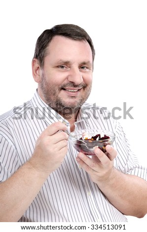 Cheerful middle aged man is fond of a beet salad. Vertical side portrait of bearded man with salad bowl in left hand and tea spoon in right on white background