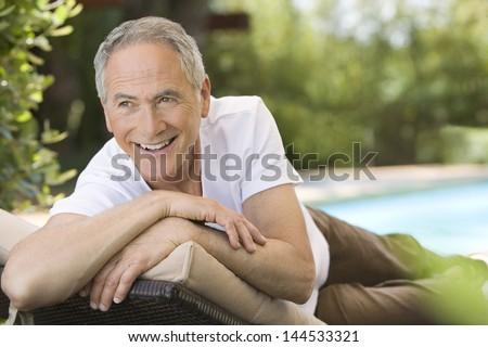 Cheerful middle aged man reclining on deck chair in garden - stock photo