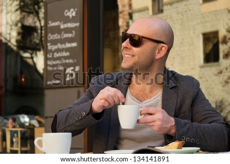 Cheerful middle-aged man with coffee cup in street cafe - stock photo