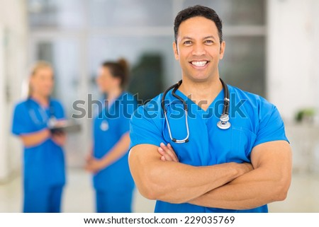 cheerful middle aged medical doctor with arms crossed in clinic - stock photo