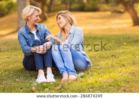 cheerful middle aged mother and young daughter chatting at the park - stock photo