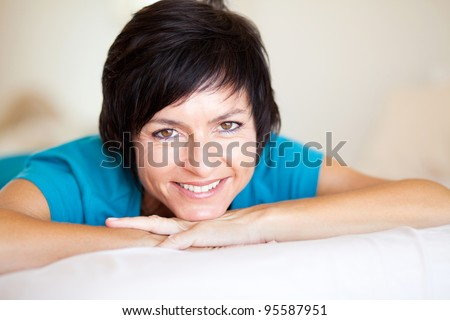 cheerful middle aged woman lying on bed - stock photo