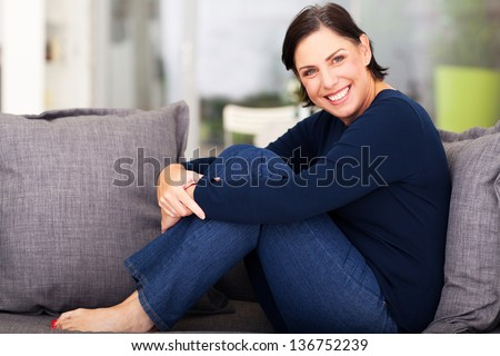 cheerful middle aged woman relaxing on a sofa - stock photo