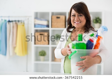 Cheerful mixed-race housewife with basket of various cleaning supplies - stock photo