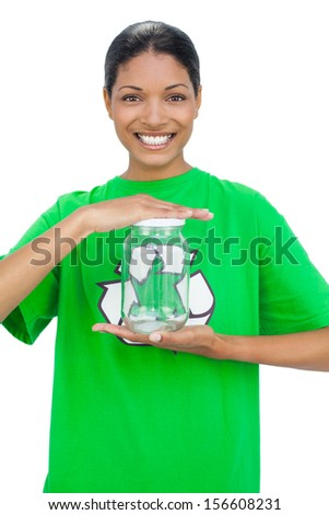 Cheerful model wearing recycling tshirt holding glass pot on white background - stock photo