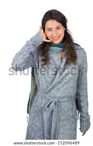 Cheerful model with winter clothes making phone call gesture while posing on white background - stock photo