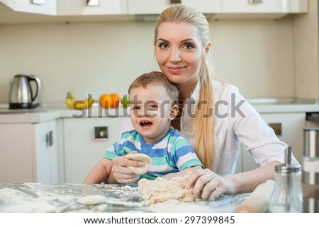 Cheerful mom and her small son are baking cookies. The woman is holding toddler on her knees. They are smiling and looking at the camera with joy. Copy space in left side