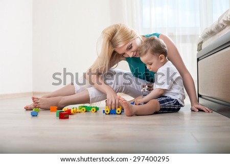 Cheerful mom is playing with her kid in bedroom. The boy is looking at toys with interest. His mamma is smiling happily