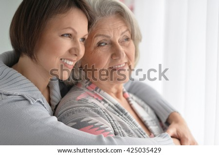 cheerful mother and adult daughter - stock photo