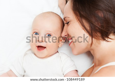 cheerful mother and baby lying in bed - stock photo