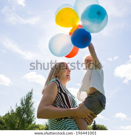 Cheerful mother and daughter playing with colorful balloons against cloudy sky - stock photo