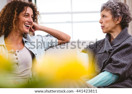 Cheerful mother and daughter sitting on sofa at home - stock photo