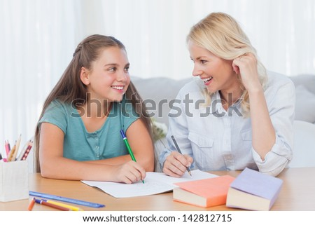 Cheerful mother and daughter writing together in the living room - stock photo