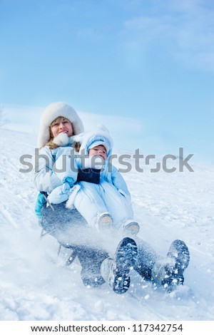 Cheerful mother and her toddler son sliding down the winter hill