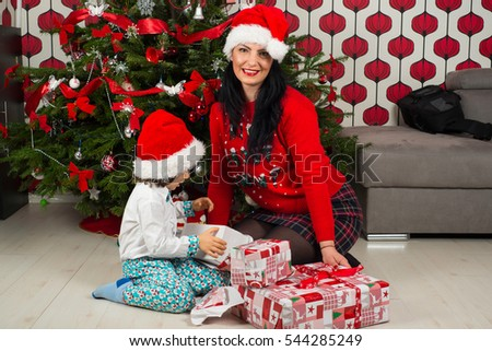 Cheerful mother and kid opening Christmas presents