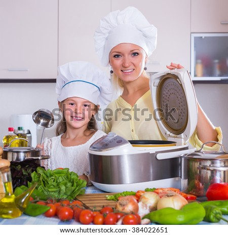 Cheerful mother and little daughter in chefs hat with crockpot in home kitchen  - stock photo