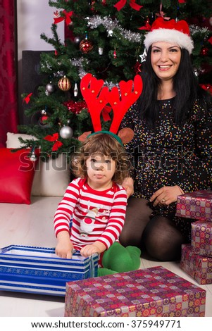 Cheerful mother and son at Christmas celebrating and opening presents - stock photo