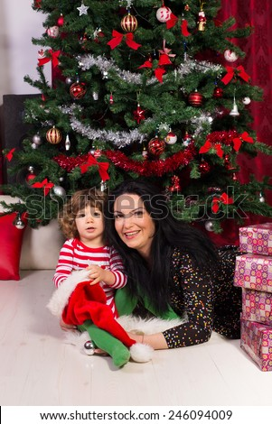 Cheerful mother and toddler son sitting together under Christmas tree - stock photo