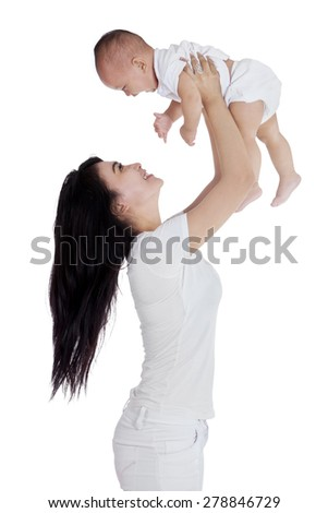 Cheerful mother having fun with her little daughter in the studio, isolated on white background