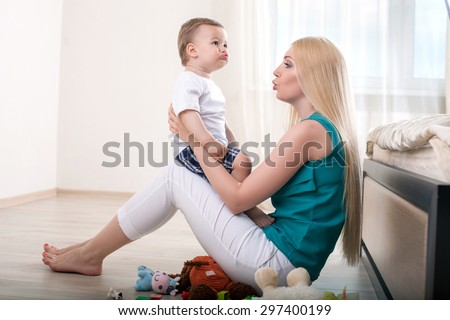 Cheerful mother is teaching her male toddler to talk. She is holding him and sitting on flooring. The mom is looking at her child with love - stock photo