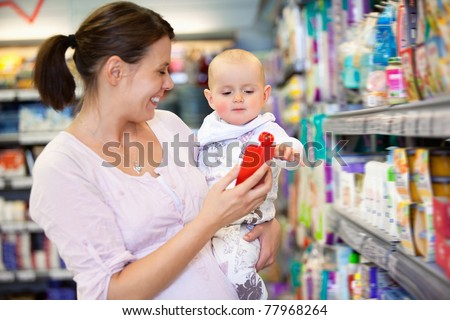 Cheerful mother playing with baby and spending time in shopping store - stock photo