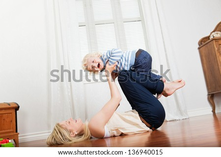 Cheerful mother playing with her cute loving baby boy at home - stock photo