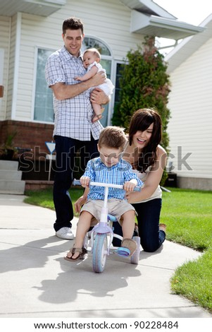 Cheerful mother teaching son to ride tricycle while husband holds daughter in background - stock photo