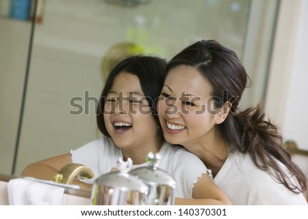 Cheerful mother with daughter looking at reflection in the bathroom mirror - stock photo