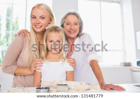 Cheerful mothers and daughters cooking together in the kitchen - stock photo